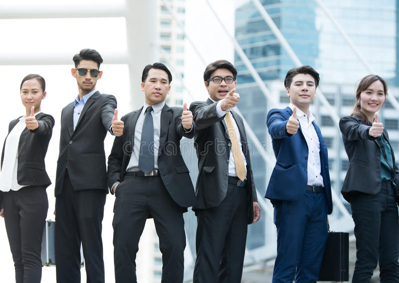 Successful business people with thumbs up and smiling stock photography