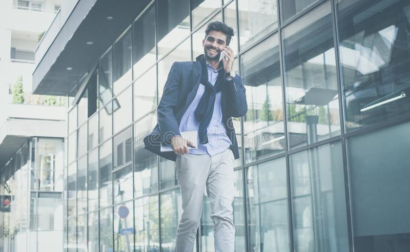 Successful business talk over the phone. Happy businessman on street hurry on work and talking on phone royalty free stock photography