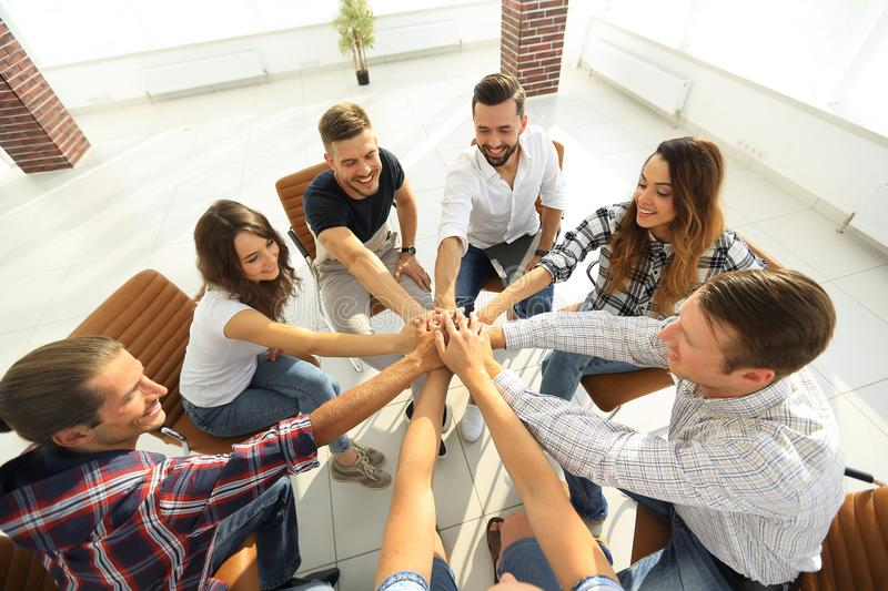 Successful business team.the concept of unity. Successful business team sitting in the middle of the office and hands clasped together royalty free stock image