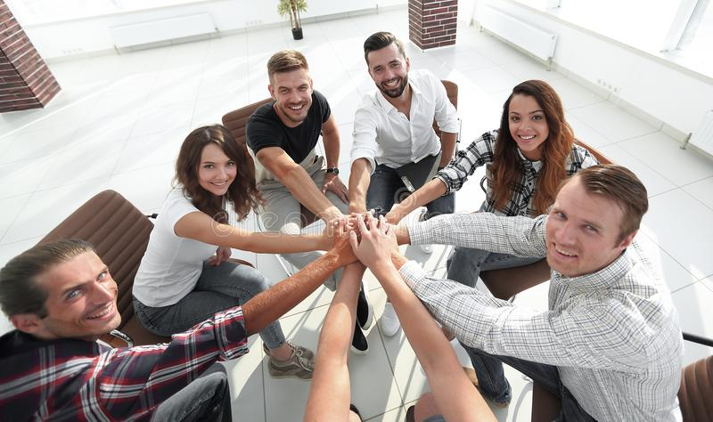 Successful business team.the concept of unity. Successful business team sitting in the middle of the office and hands clasped together stock photography