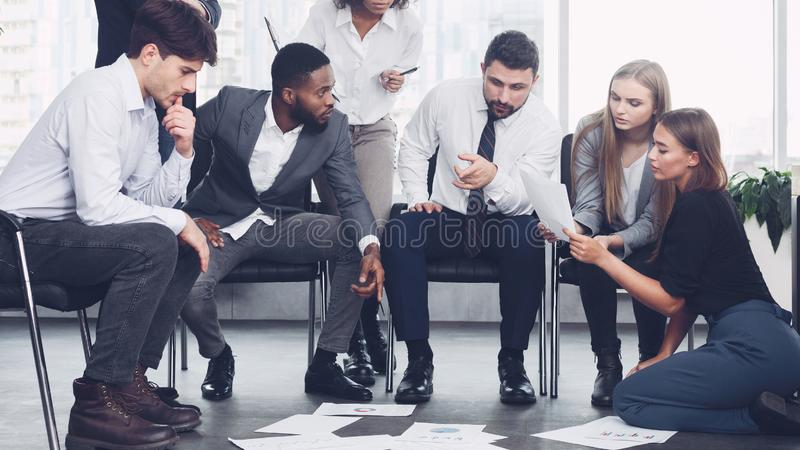 Successful business team creating new project in office. Successful business team creating new project, looking at papers on floor in search of ideas royalty free stock photo