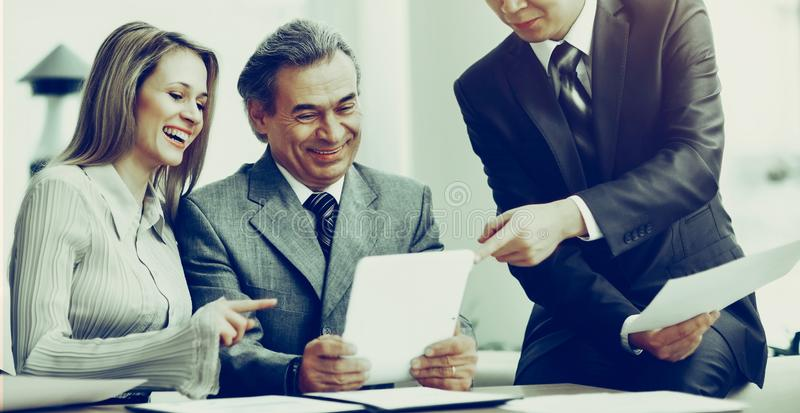 Successful business team discussing work plan using a tablet royalty free stock photos