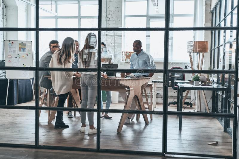Successful business team. Full length of young confident business people discussing something while working behind the glass wall stock photo