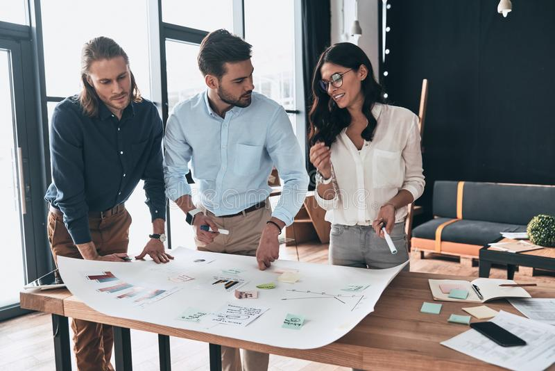 Successful business team. Group of young confident business people discussing something while working with blueprint in the office stock image