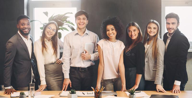 Successful business team looking at camera in office stock image