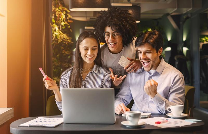 Successful business team looking at laptop happily stock images