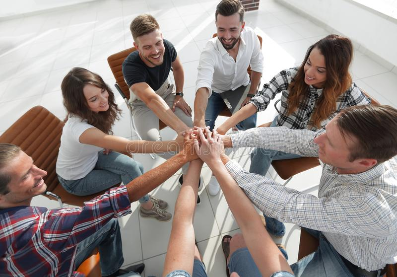 Successful business team.the concept of unity. Successful business team sitting in the middle of the office and hands clasped together royalty free stock photos