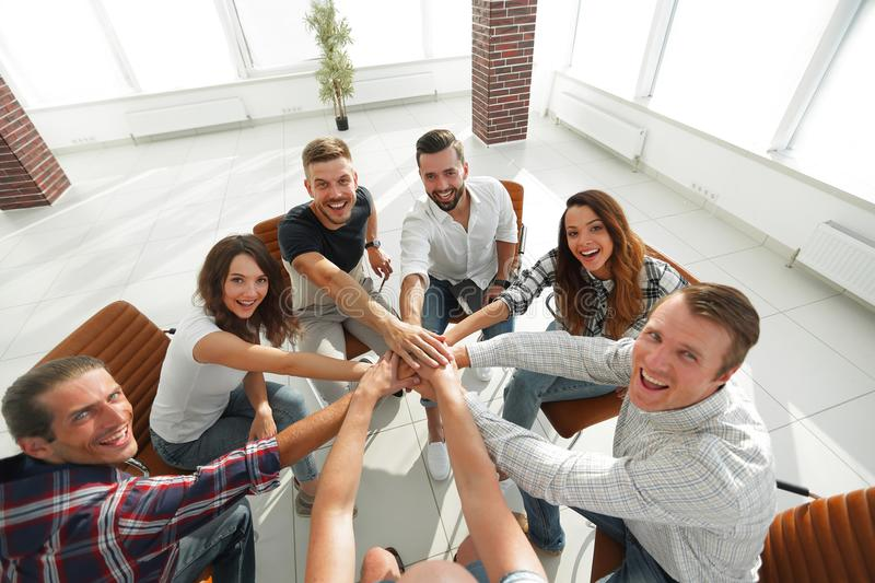 Successful business team.the concept of unity. Successful business team sitting in the middle of the office and hands clasped together royalty free stock photo