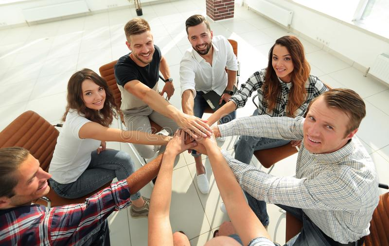 Successful business team.the concept of unity. Successful business team sitting in the middle of the office and hands clasped together royalty free stock images
