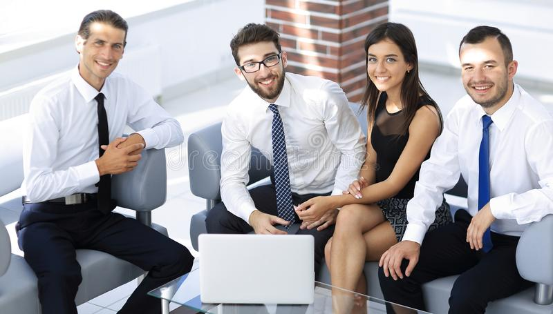 Successful business team sitting in office lobby stock images