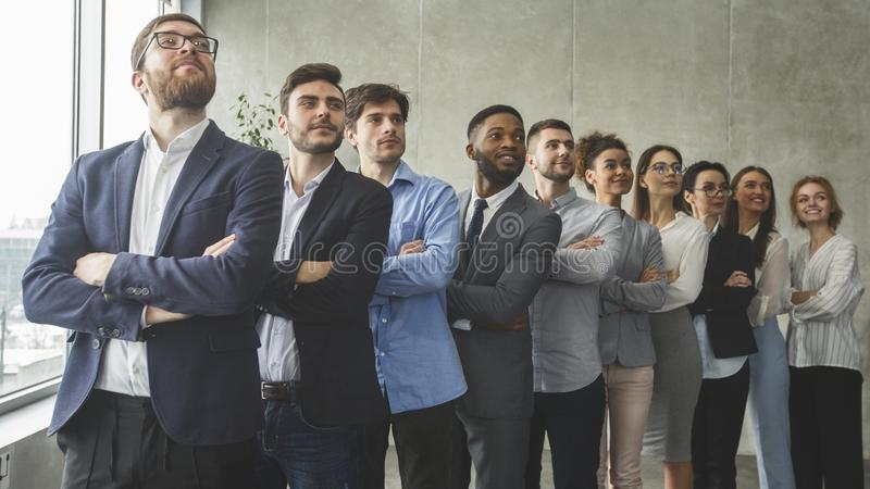 Successful business team standing in row headed with boss. Successful business team standing in row with crossed arms and headed with boss, looking aside in stock photography