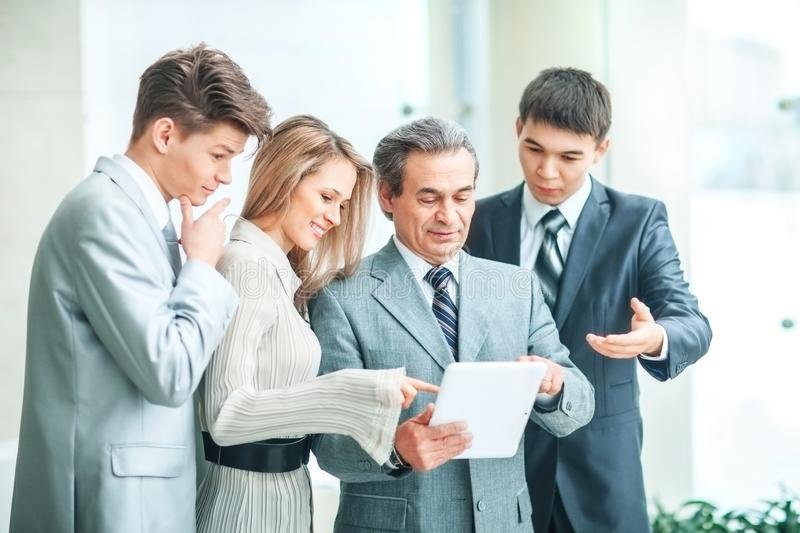 Successful business team with tablet and documents discussing business matters stock photography
