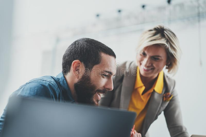 Successful business team at work. Group of young business people working with laptop and communicating together in royalty free stock photography