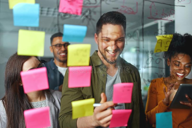 Group of smiling casual business people planning and writing project and ideas over the sticky notes pasted on glass stock photos