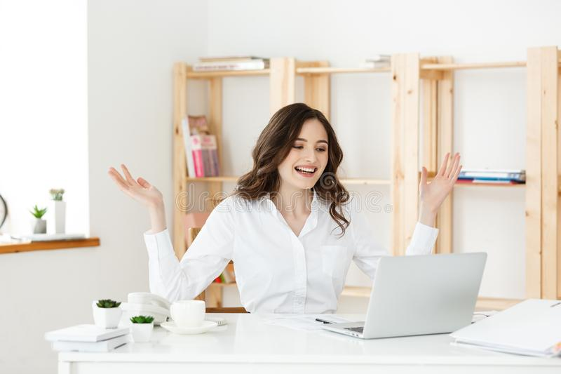 Successful business woman with arms up sitting in modern office. royalty free stock photos