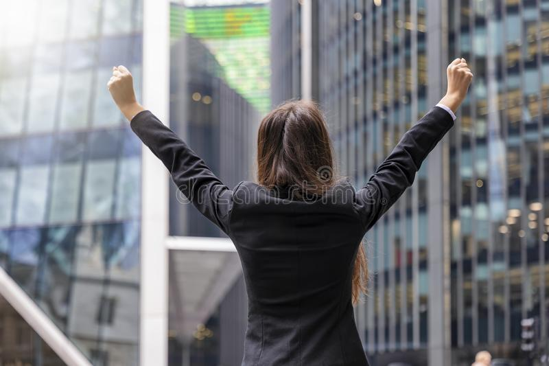 Successful business woman concept. Woman in corporate outfit cheers with raised arms in front of modern office buildings royalty free stock photos