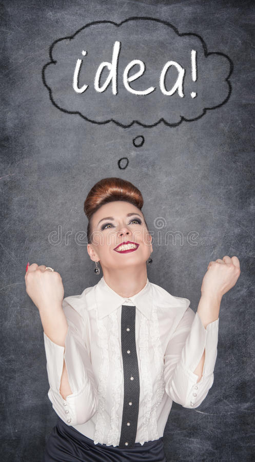 Successful business woman having idea. On the blackboard background royalty free stock photography