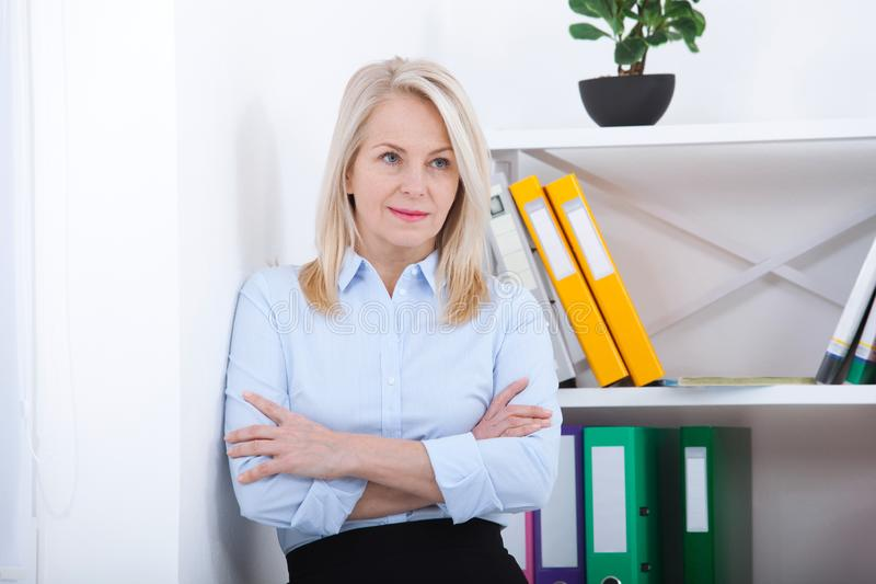 Successful business woman looking confident and smiling. business woman in blue shirt looking friendly into camera royalty free stock images