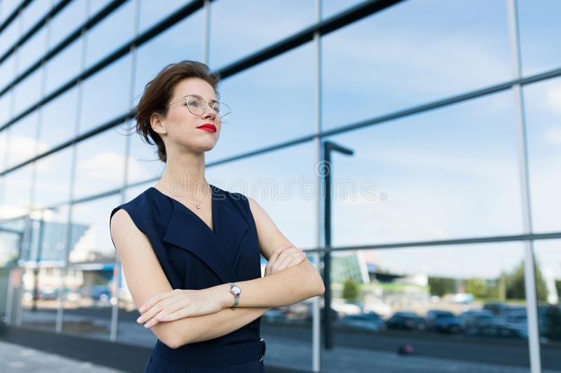 Successful business woman posing against the backdrop of a mirror building with reflection of clouds and sky.  stock photos