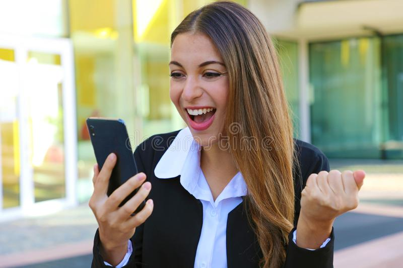Successful business woman reading good news on smartphone and celebrate feeling happy royalty free stock images