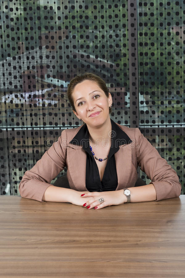 Successful business woman sitting at desk royalty free stock image