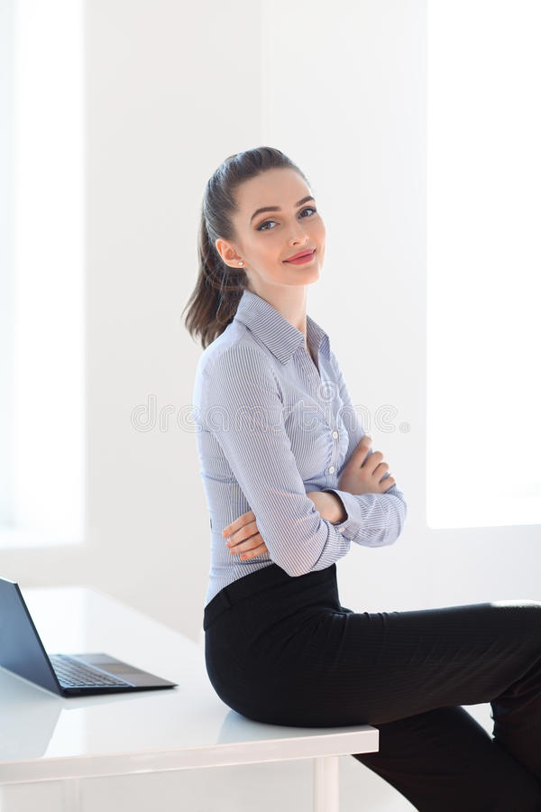 Successful business woman sitting on desk in office background royalty free stock photos