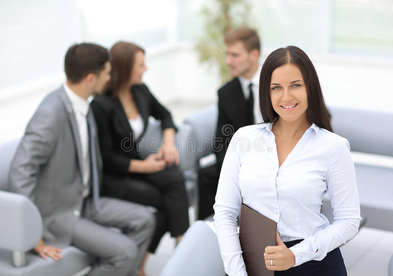 Successful business woman standing with her staff in background stock image