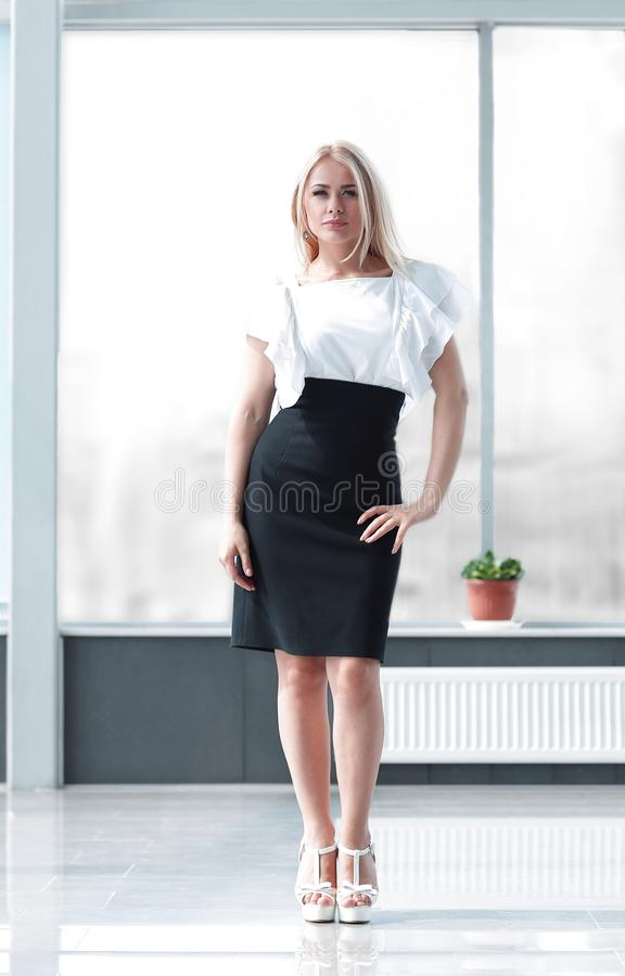 Successful business woman standing in the spacious lobby of the office. royalty free stock photography