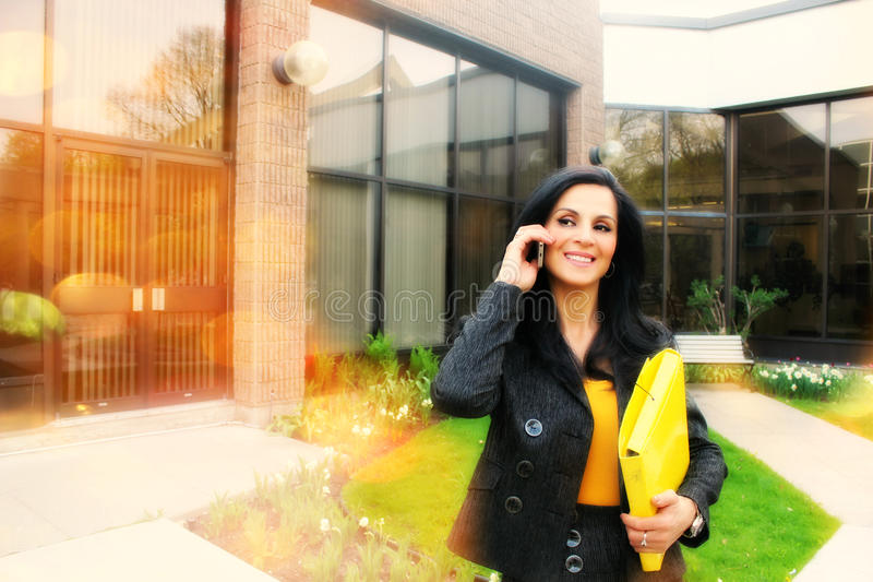 Successful business woman talking on smartphone. Smiling business woman holding a notebook and talking on the phone in company quarters stock photos
