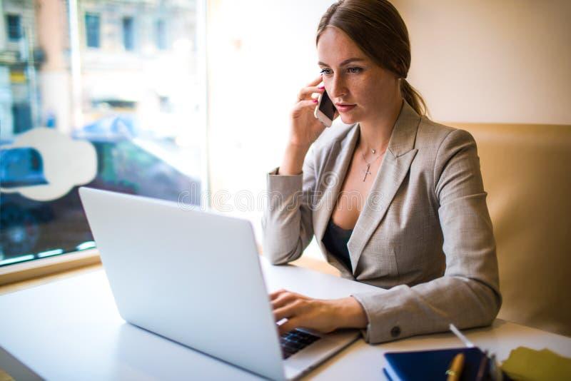 Female editor having cellphone conversation stock image
