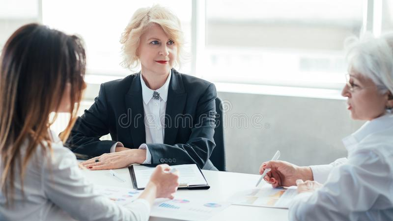 Successful business women meeting report. Successful business women at meeting. Financial report. Mature female boss reviewing sales performance. Female oriented royalty free stock images