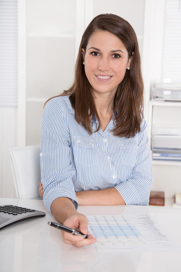 Successful business: young woman in blue blouse sitting at desk stock photography
