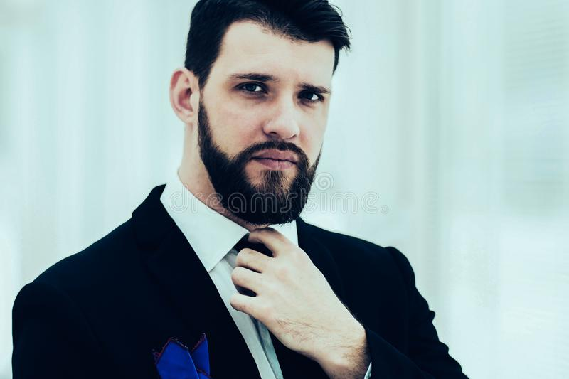 Successful businessman adjusting his necktie while standing near stock photos