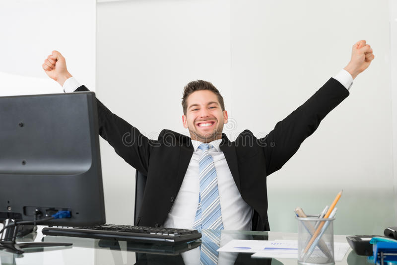 Successful businessman with arms raised at desk royalty free stock photography