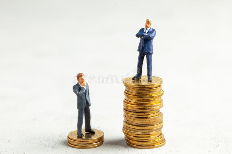 Successful businessman with big profits on stack of gold coins and less successful businessmen with small companies. The concept stock photography