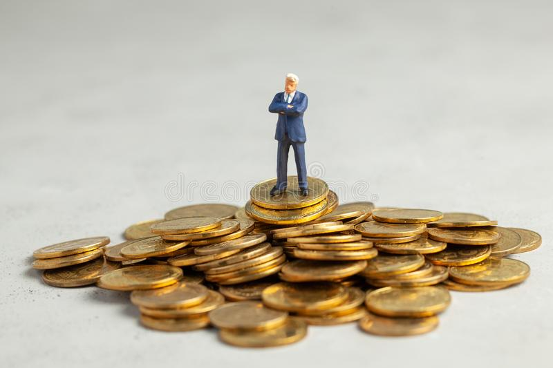 Successful businessman with big profits is standing on pile of gold coins. Successful investment of money in the company royalty free stock images