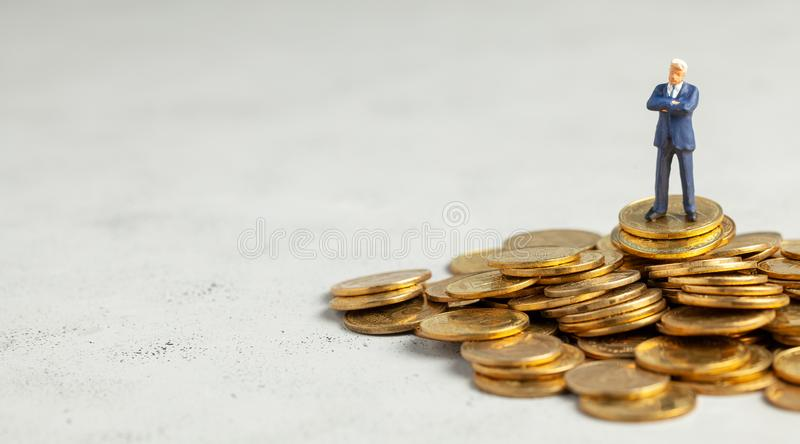 Successful businessman with big profits is standing on pile of gold coins. Successful investment of money in the company. Copy stock photo