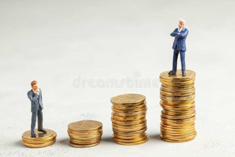 Successful businessman with big profits at the top of the stairs by coins and less successful businessmen with small stock photo