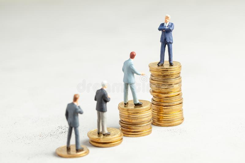Successful businessman with big profits at the top of the stairs by coins and less successful businessmen with small companies. Adequate investment in the stock image