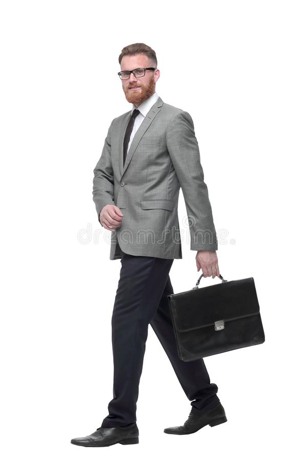 Successful businessman with briefcase goes forward. isolated on white royalty free stock photography