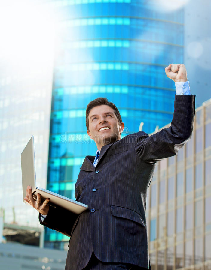 Successful businessman with computer laptop happy doing victory celebrating success. Young attractive and successful businessman in suit and tie with computer royalty free stock images