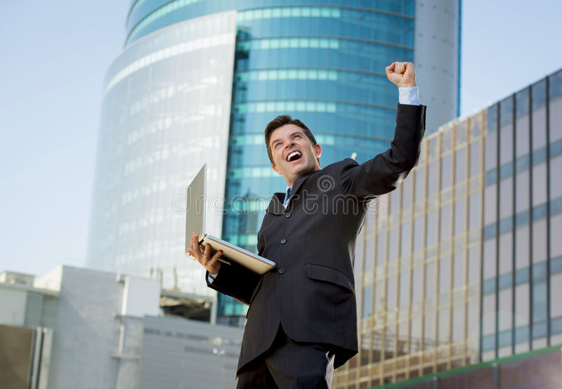 Successful businessman with computer laptop happy doing victory sign. Young attractive and successful businessman in suit and tie with computer laptop happy and stock photos