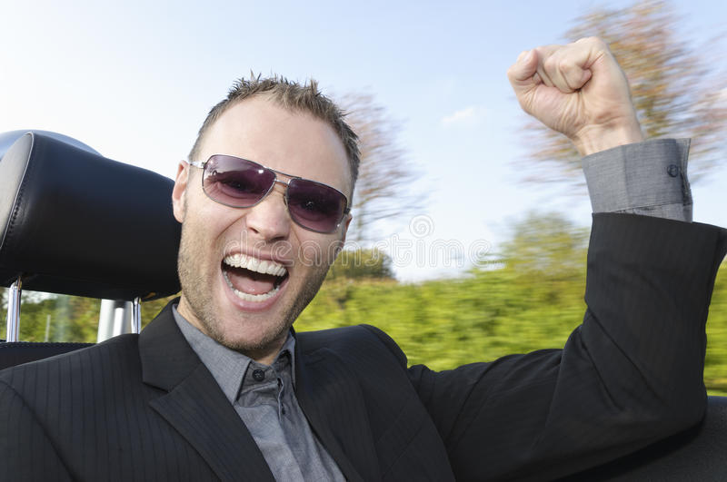 Successful businessman in a convertible stock photo