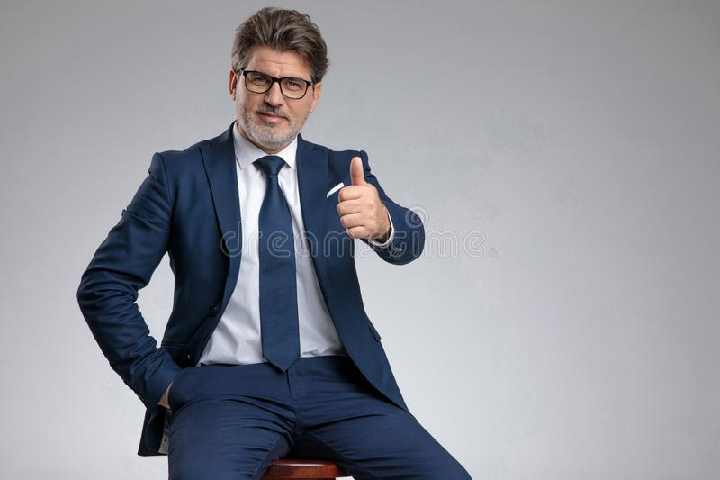 Successful businessman giving a thumbs up stock image