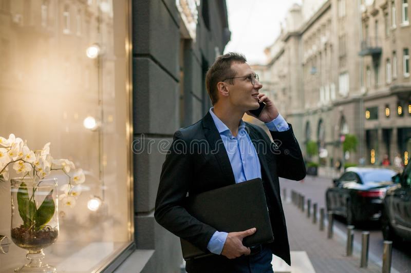Successful businessman in suit with laptop talking on the phone and smiling in the city stock image