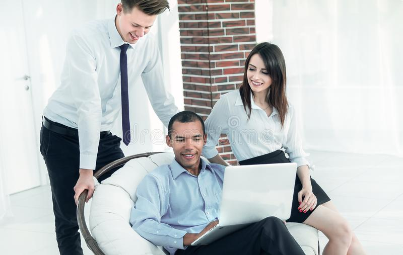 Successful businessman with his assistants in a discussion of the information from the laptop. stock photos