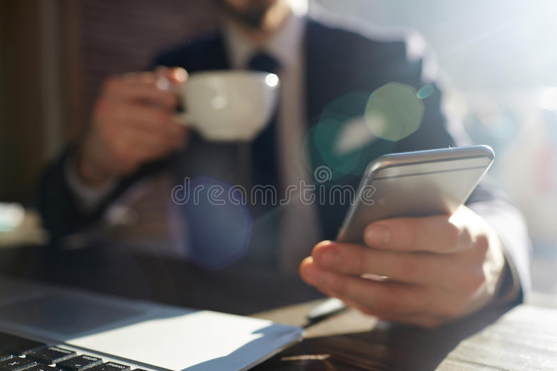 Successful Businessman Holding Smartphone in Sunlight stock image