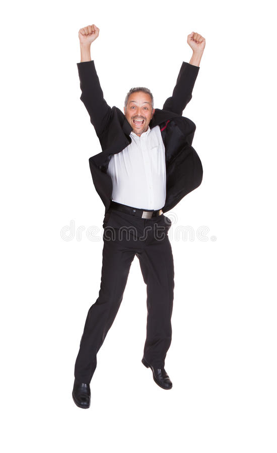 Successful businessman jumping with hands raised royalty free stock image