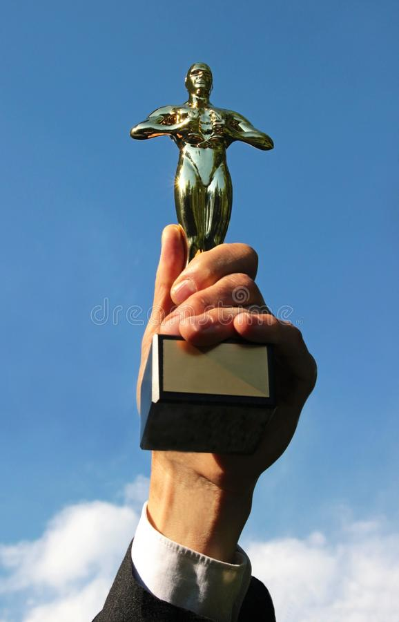 Successful businessman lifting an oscar statuette up in the air. Successful businessman with a white shirt and a black jacket lifting an oscar statue up into the royalty free stock photography