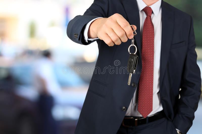 Successful businessman offering a car key. Close-up of driver`s hand showing key.  stock photography